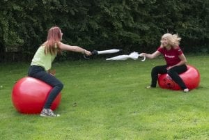 Kat and Gemma on space hoppers with umbrellas